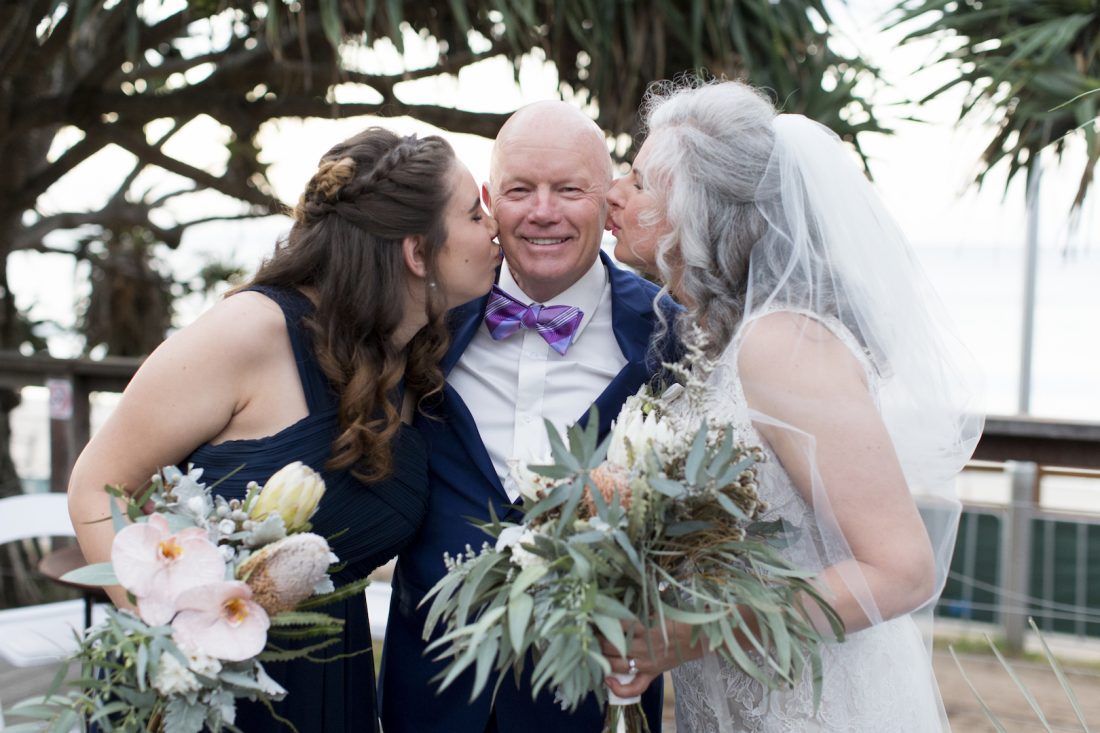 Groom enjoying a kiss from wife and daughter